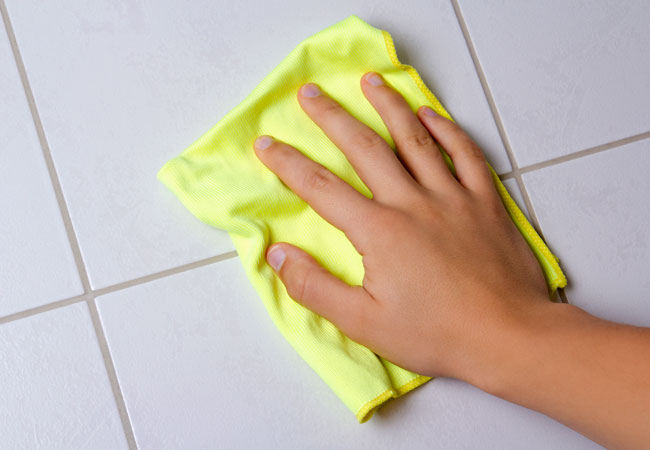 male-hand-with-yellow-rag-cleaning-the-bathroom-tiles-000076737323_Medium2