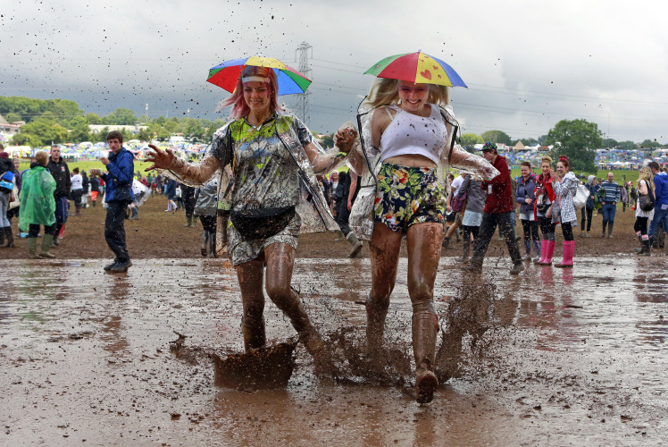 Festival goers splash through a muddy puddle at Worthy Farm in Somerset, on the third day of the Glastonbury music festival